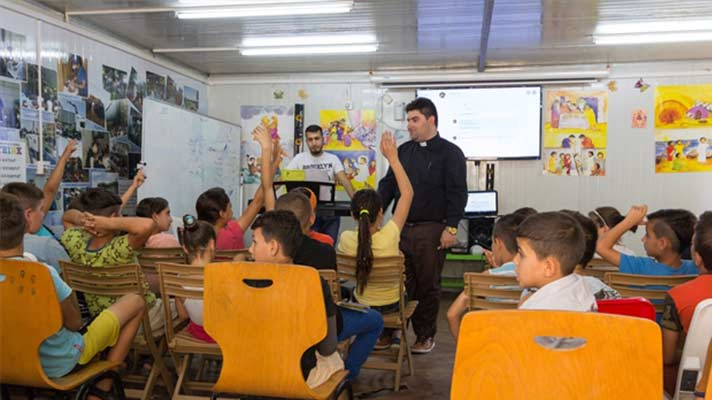 Father Daniel with displaced children in Iraq.