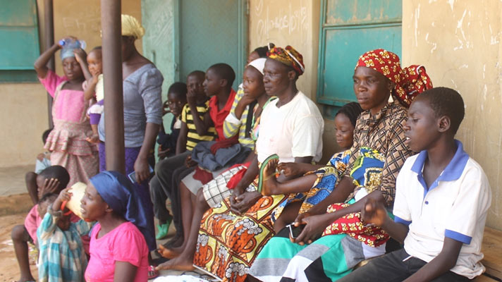 Traumatised people sit around in one of the IDP camps