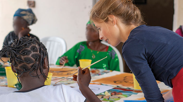 The artist Hannah Rose Thomas working with women in Nigeria to help them paint their self-portraits.