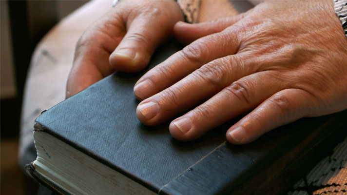 Hea Woo's hands on her Bible.