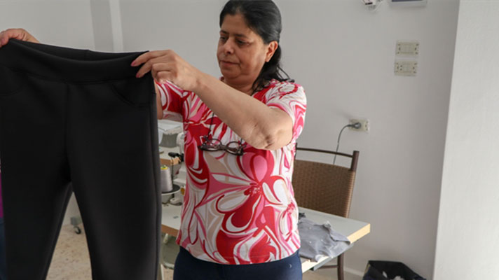 Hala holds up a pair of trousers.